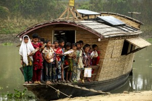 Students of class one on the boat school, pose for a photograph, after the end of their classes. The floating boat school moves from one area to another and goes to the children for giving education as the children don't go to the traditional school because of lack of communication during flooding, Billdohor, Natore.Billdohor, Natore.